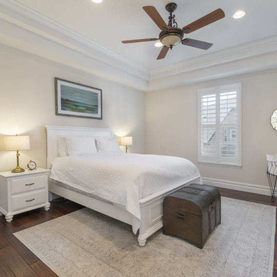 home inspection - bedroom, white bed comforter, ceiling fan, run and trunk at the end of the bed