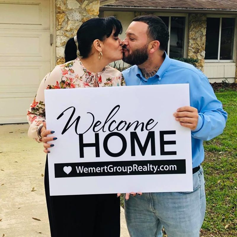 couple kissing and holding up their welcome home sign in front of their new beautiful home